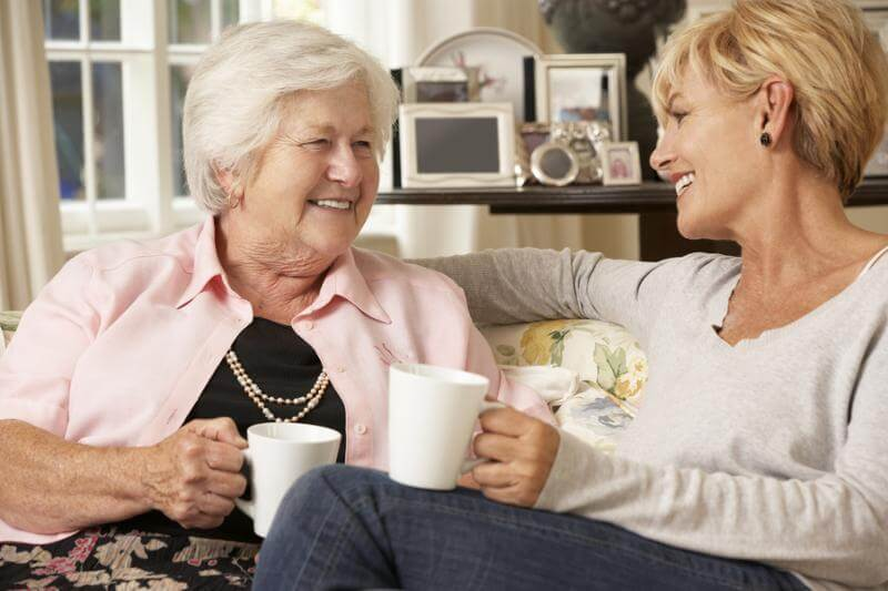 Mother and daughter sitting on sofa together drinking tea