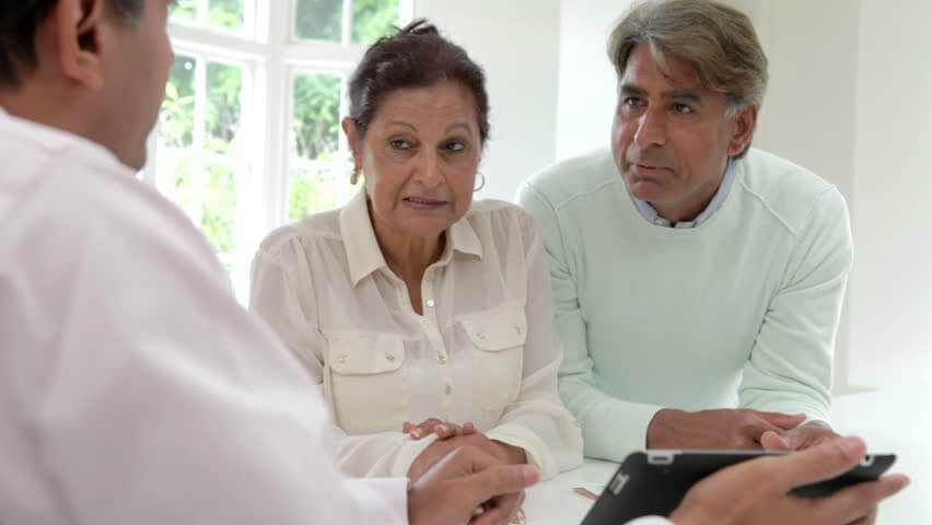 Senior Asian Indian couple discussing document with financial advisor